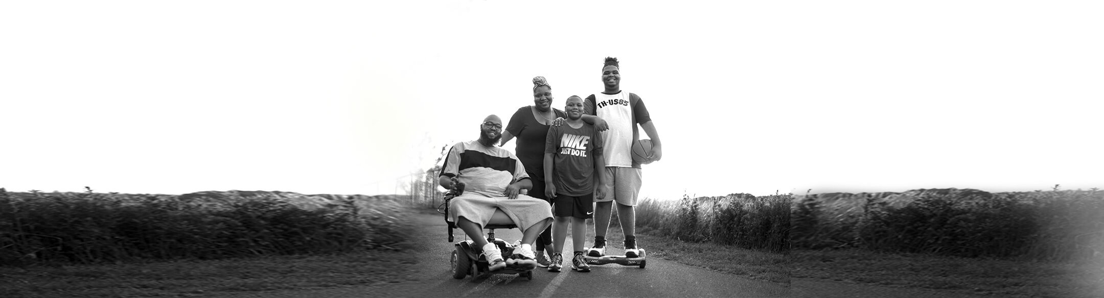 Princeton patient living with Pompe disease sitting in a wheelchair with his family